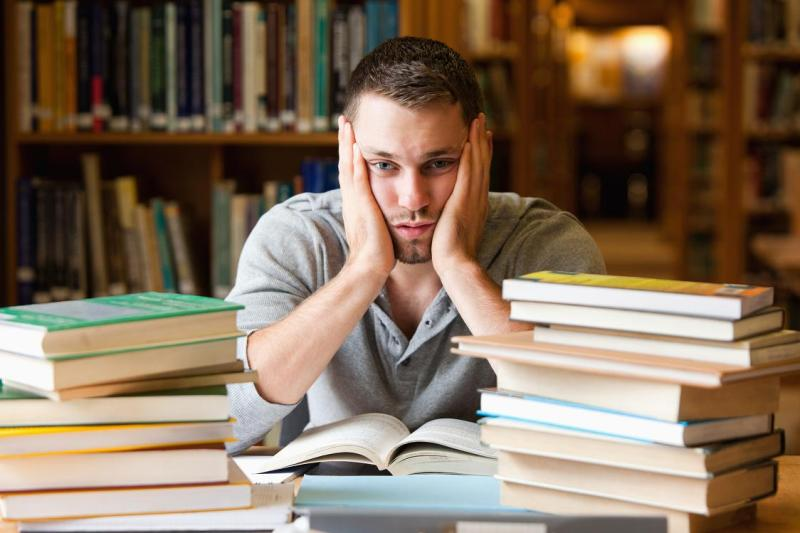 Depressed student having a lot to read looking at the camera