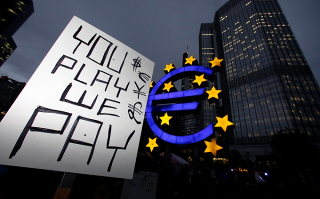 FRANKFURT AM MAIN, GERMANY - OCTOBER 18:  Protesters, inspired by the Occupy Wall Street protests in the United States display a placard in front of the headquarters of the European Central Bank (ECB) on October 18, 2011 in Frankfurt am Main, Germany. Around hundred protesters operate a camp outside the ECB to demonstrate against economic and financial policy